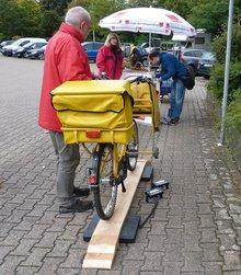 Zusteller lässt beladenes Fahrrad wiegen