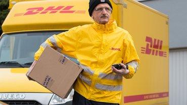 Paketzusteller vor DHL-Fahrzeug