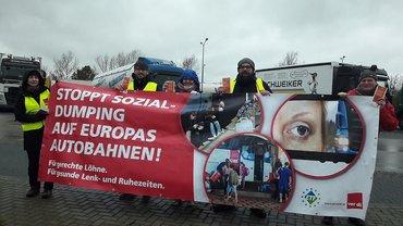 "Demonstrierende mit Plakat ""Stoppt Sozialdumping"""