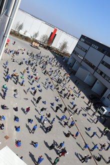 Wahl bei der ITG: Kolleg*innen stehen mit Abstand vor dem Gebäude.