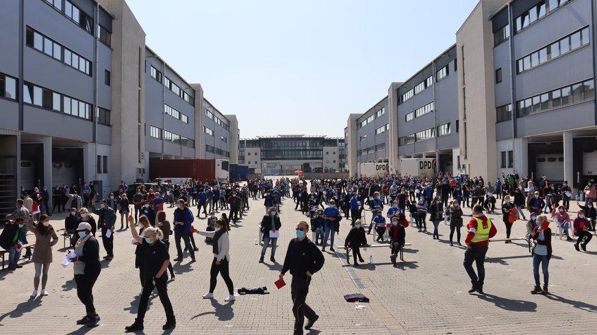 Wahl bei der ITG, Personen stehen mit Abstand vor dem Gebäude